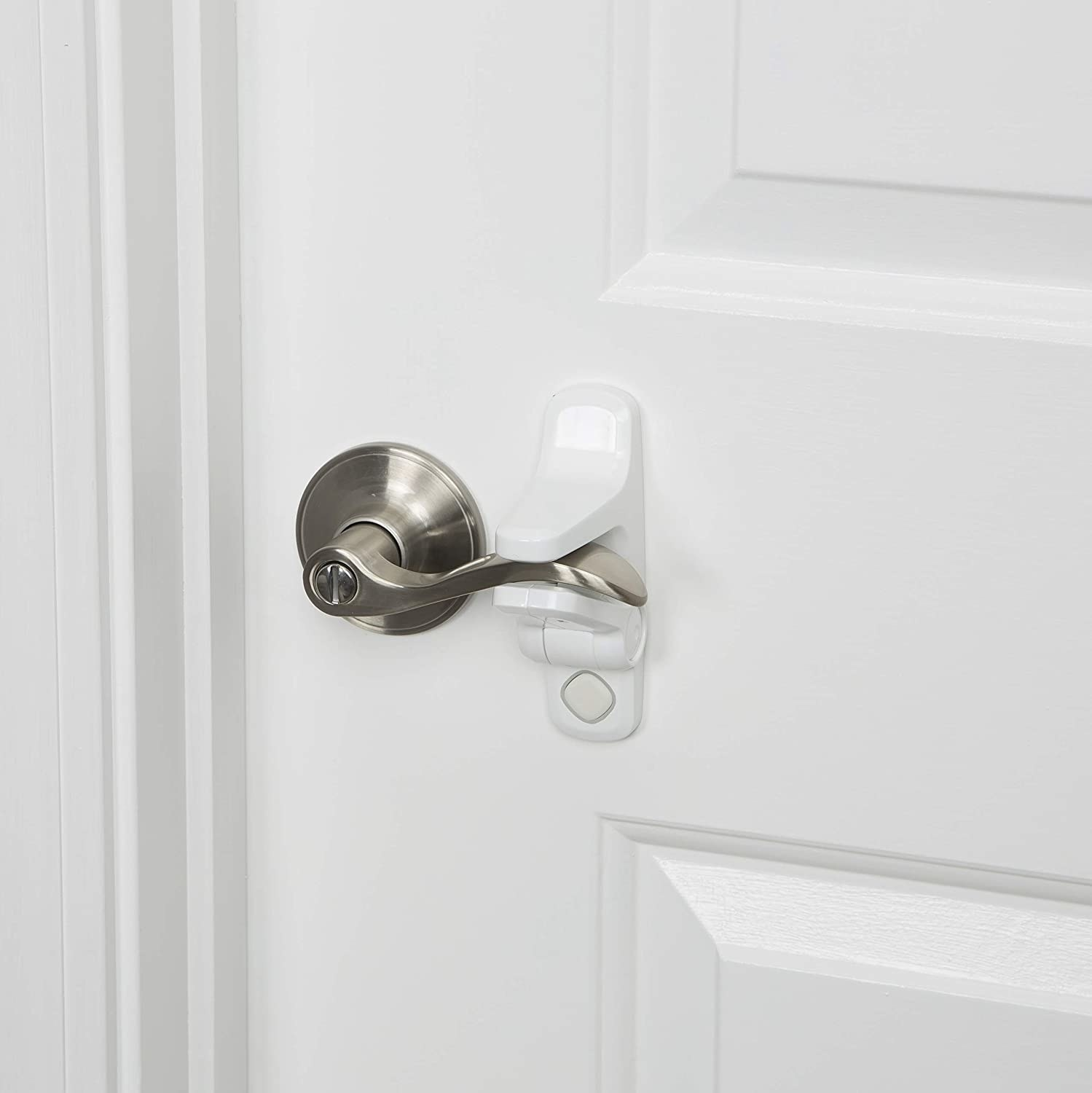 A lever door handle being held in place with a white lock. The lock is placed above and below the handle and has a push-button release system.