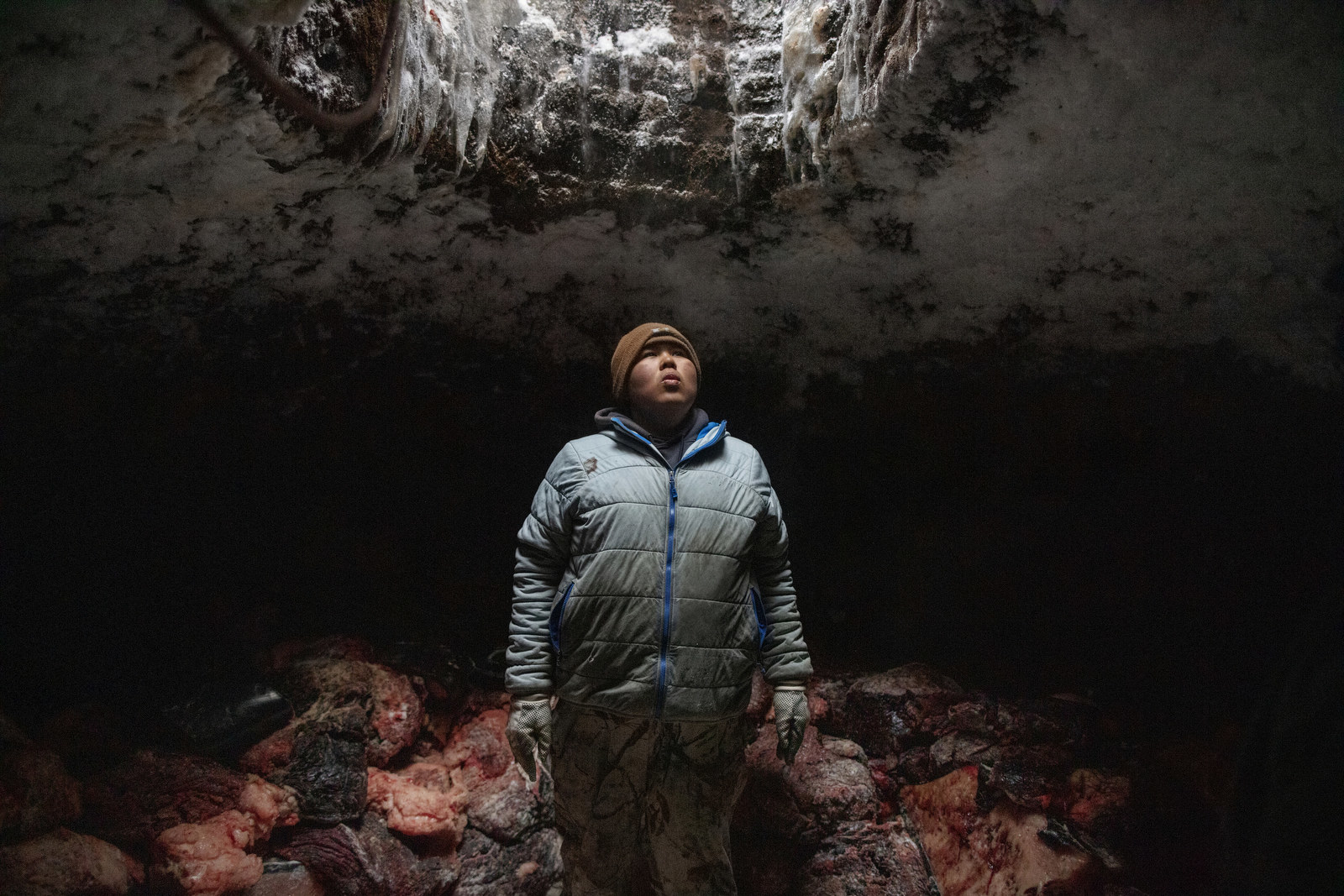 A young boy in work gloves stands in a dark ice cavern surrounded by bloody whale carcasses