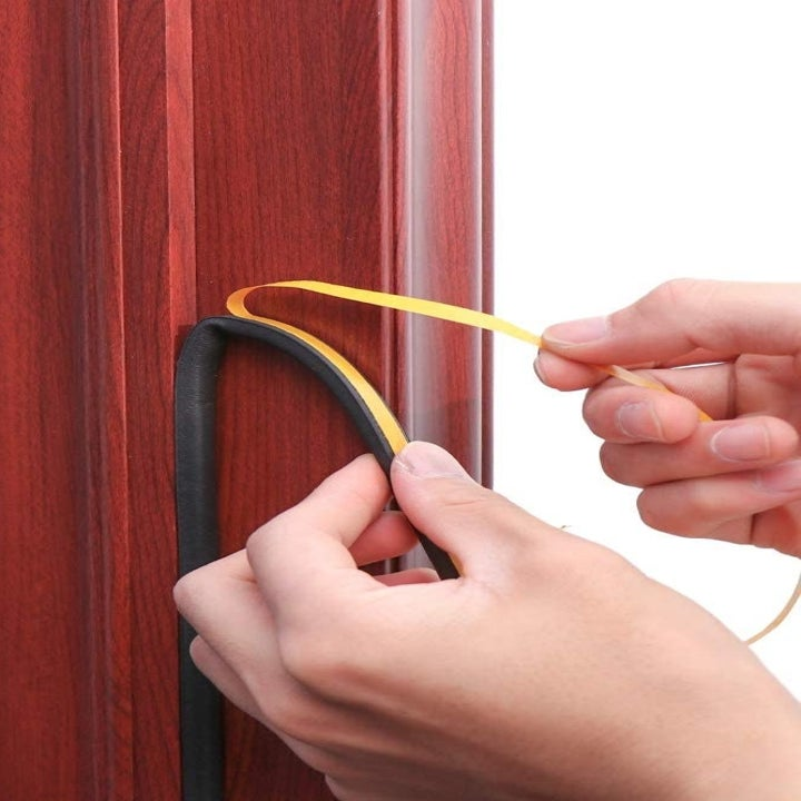 Hands peeling off the backing and sticking a black strip to a doorframe