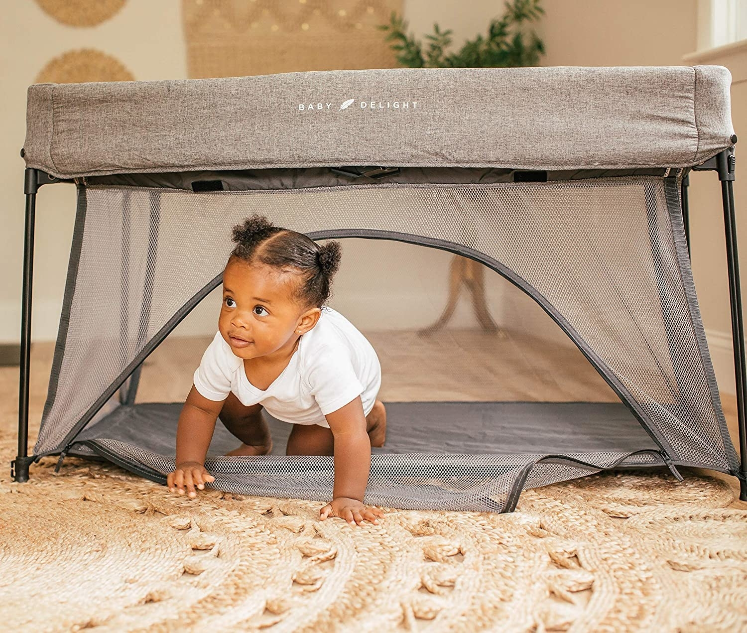 A baby crawling out of the bottom door in the mesh play space. All sides are clear mesh with a fabric cover on the top, covering the adjustable poles that create the frame