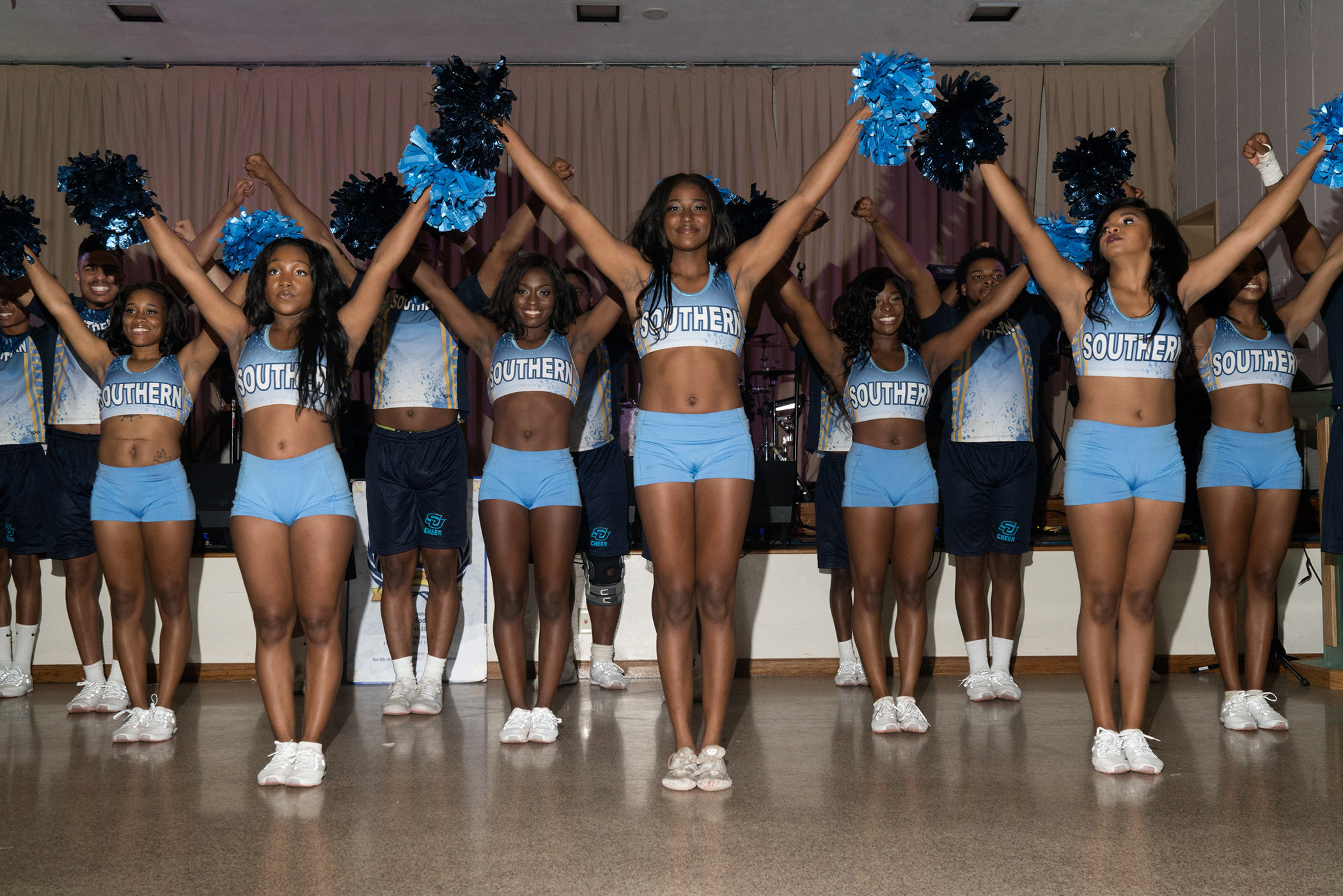 A team of cheerleaders in blue uniforms perform in their school gymnasium