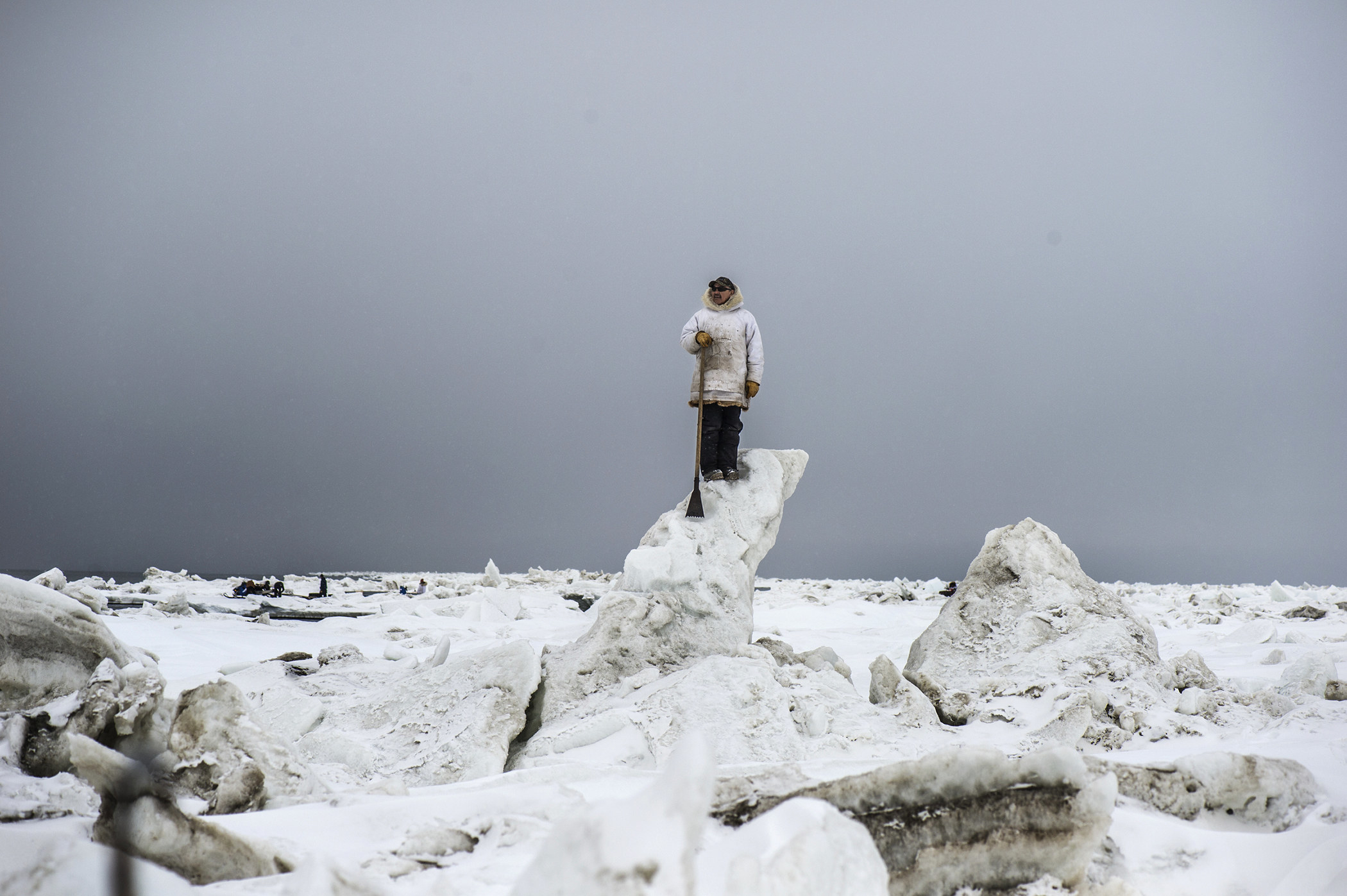 An Inuit man looks out over the ice fields of Alaska while standing on a large ice pillar