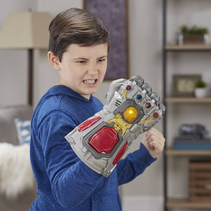 a child holding the avengers toy that looks like thanos' hand with the jewels in it
