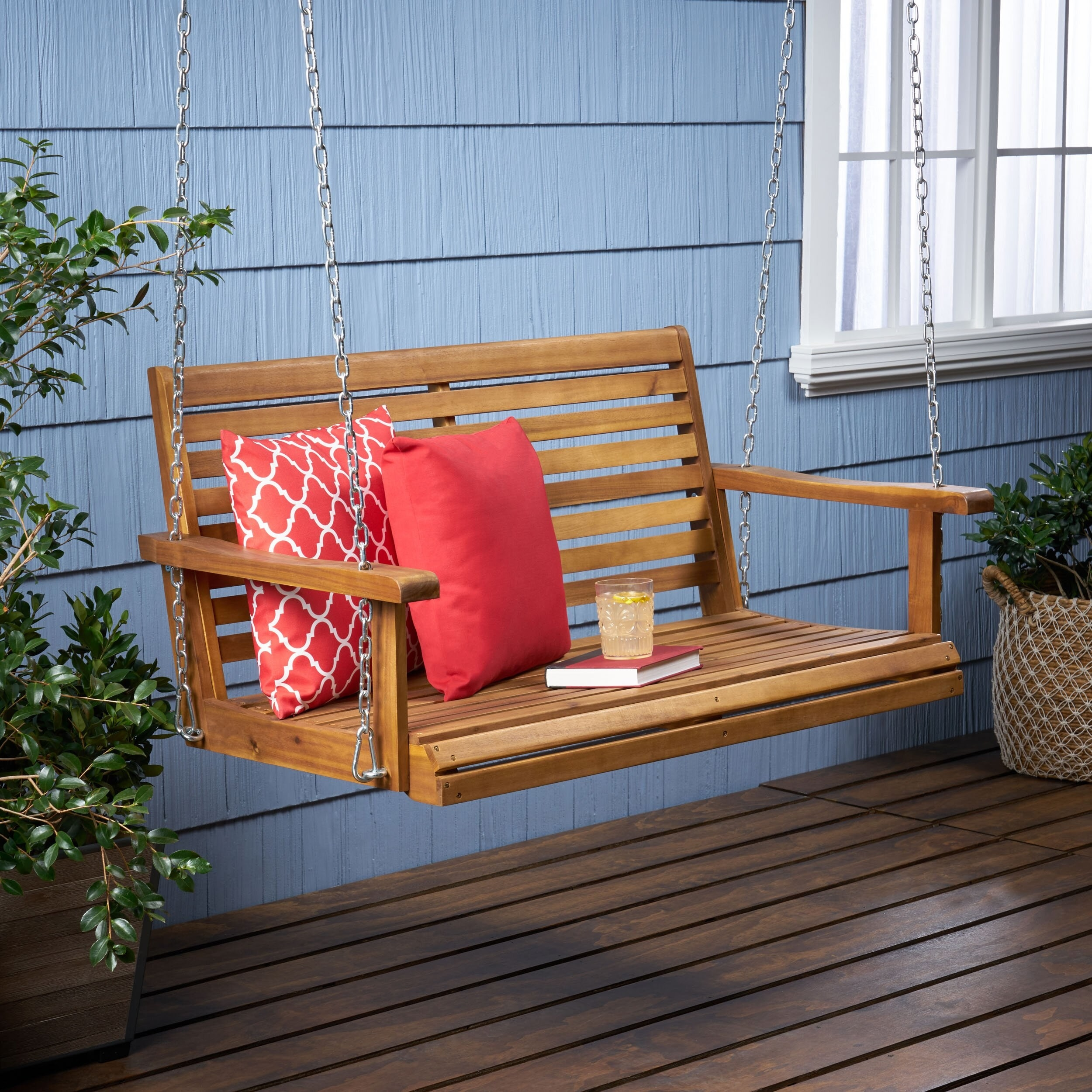 A medium wood porch swing for two people that hangs from metal chains