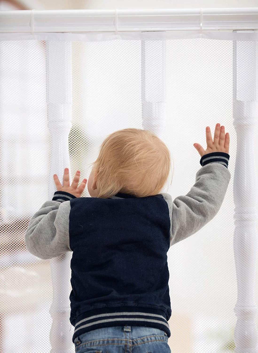A baby standing up against a railing that is covered by the mesh gate, preventing them from slipping between the poles