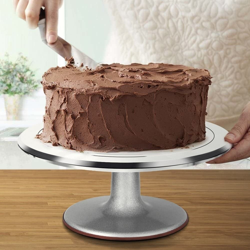 A model frosting a cake being held up by the circular cake stand