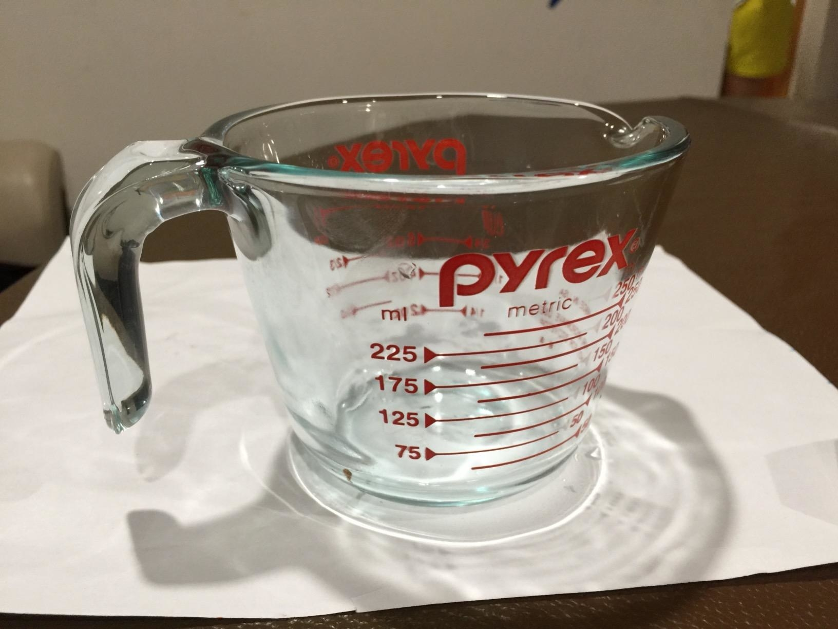 A reviewer showing the pyrex glass measuring cup, which measures up to one cup of liquid