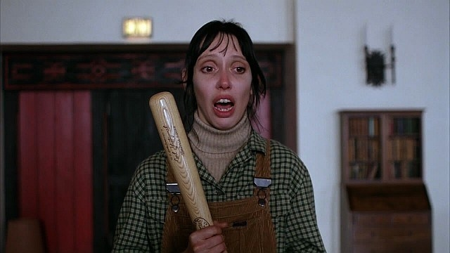 Wendy carrying a bat in the hotel, wearing overalls, with a terrifying expression on her face
