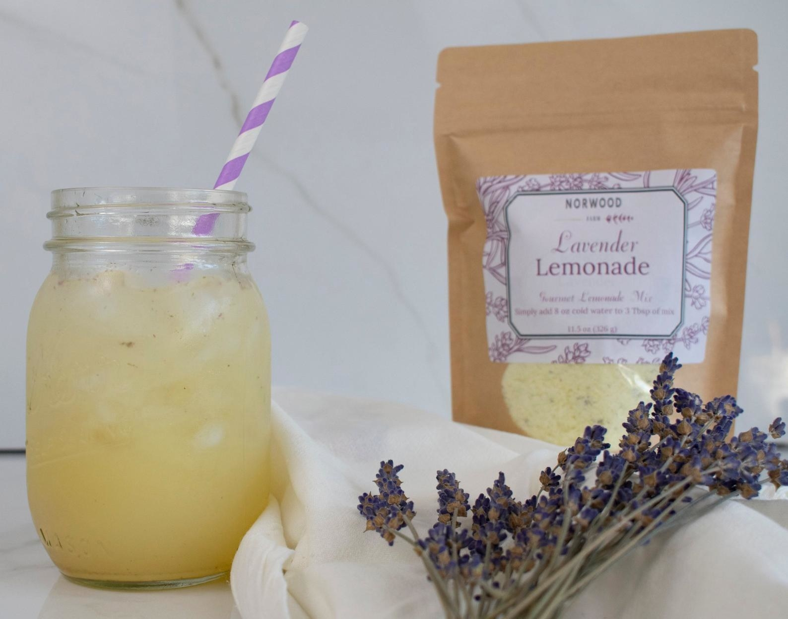 A packet of lavender lemonade with a glass of it already mixed in