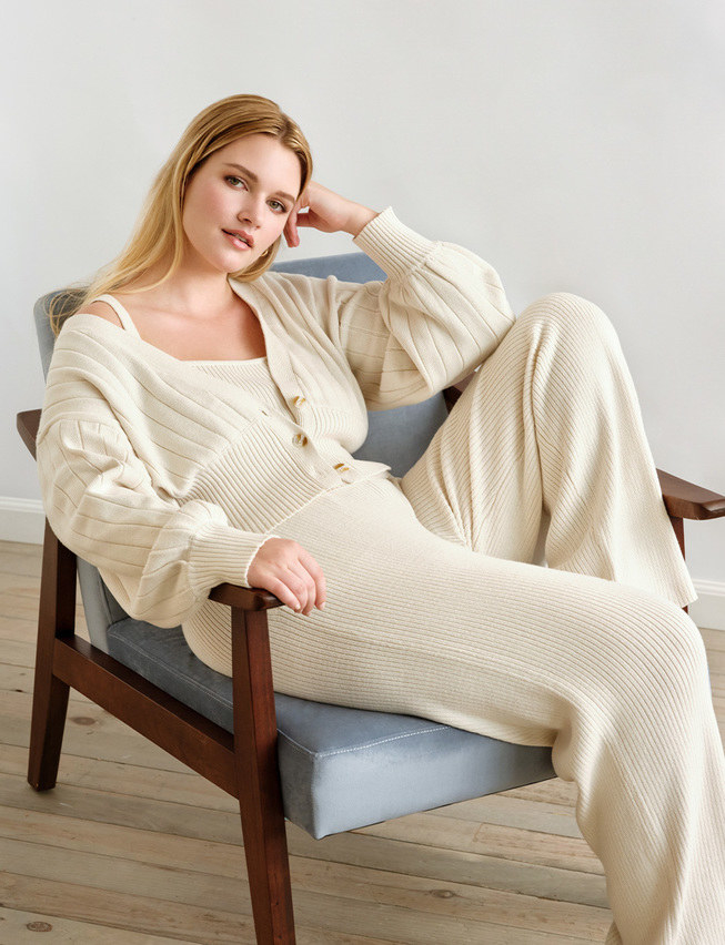 Model wearing the cream-colored ribbed pants with matching cardigan