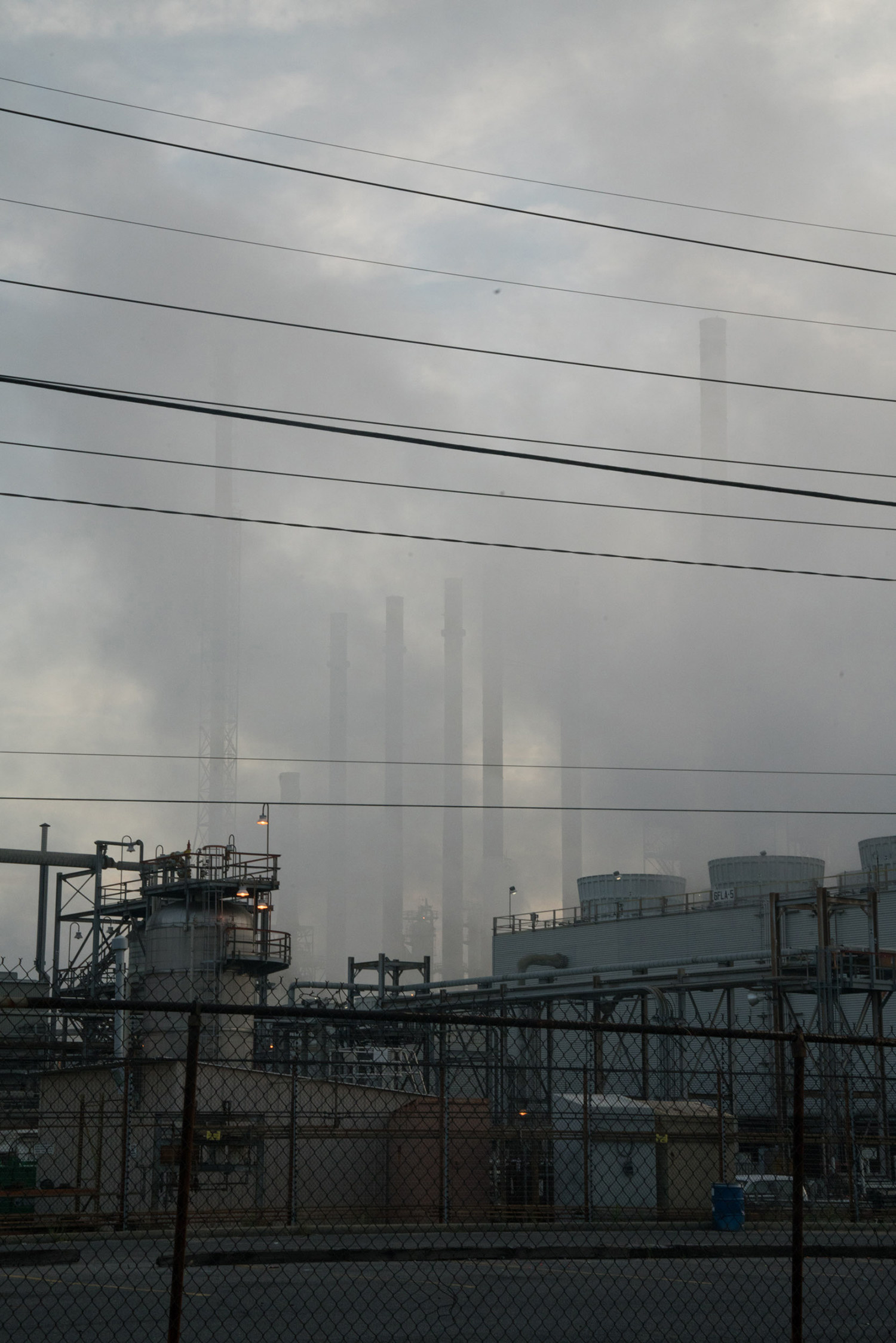 Factory smokestacks are barely visible in a cloud of smog from behind telephone wires and a metal fence