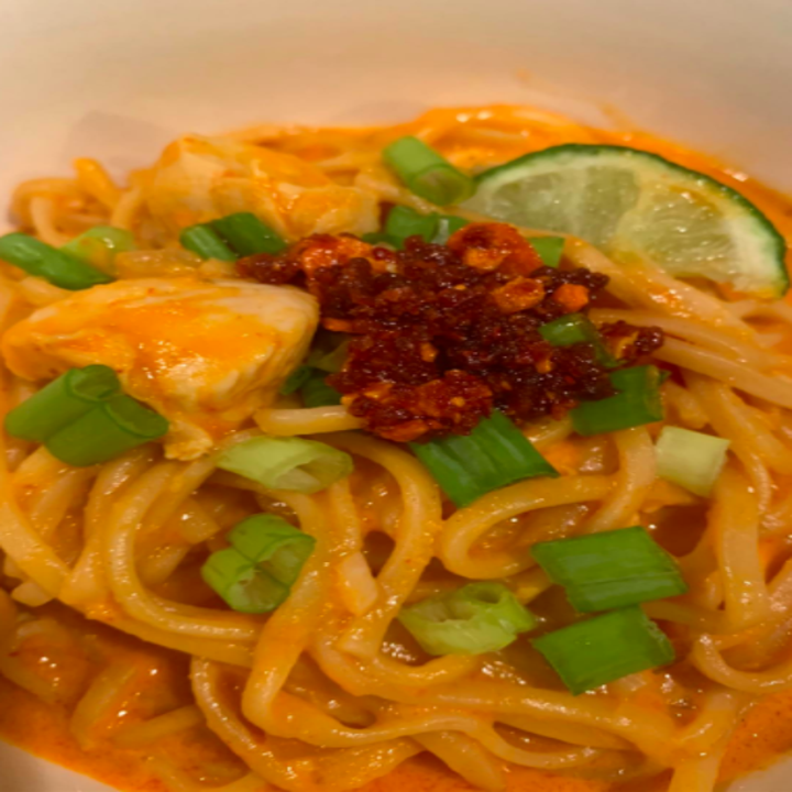A reviewer photo of a noodle dish topped with the oil, which has more of a salsa or jam-like consistency