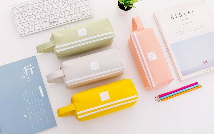 A flatlay of four pencil cases arranged neatly on a desk with other school supplies