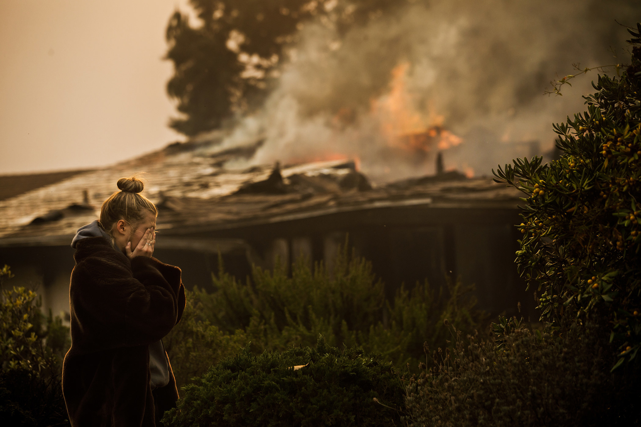 A woman wipes her tears in the foreground of a burning home