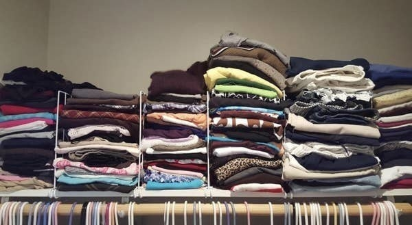 A reviewer photo of the shelves neatly separating and organizing clothes on a closet shelf
