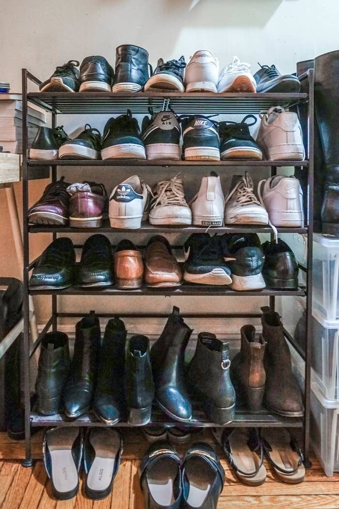 BuzzFeed Editor Yi Yang's shoe rack with five tiers holding various shoes like boots and sneakers, with some space underneath for smaller shoes like sandals