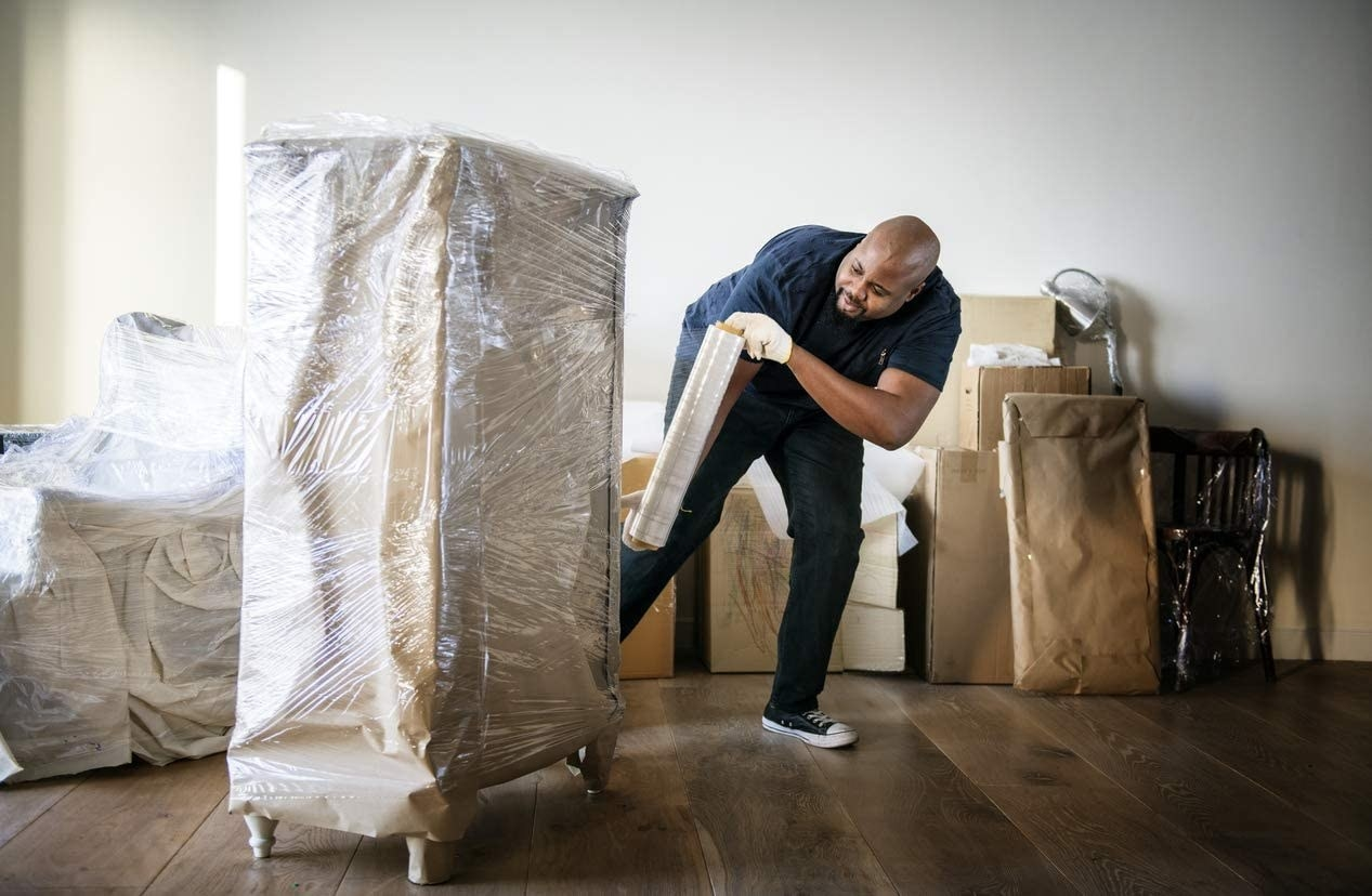 A model covering a piece of furniture on semi-transparent shrink wrap