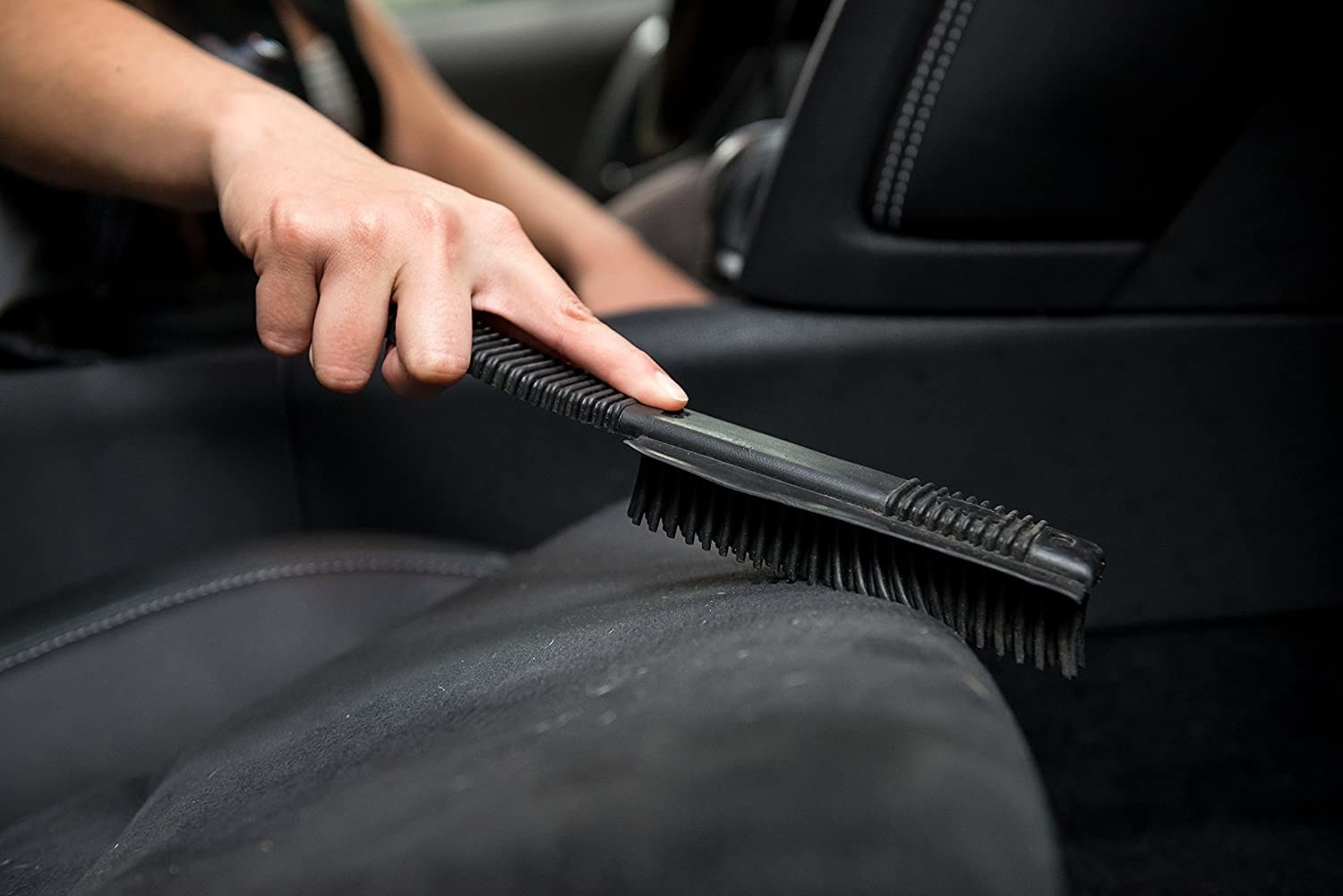 A close up of a person using the brush on dusty car seats