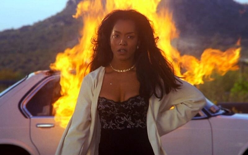 Bernie walking away from her ex-husband's car after lighting it on fire, feeling relieved and sad at the same time