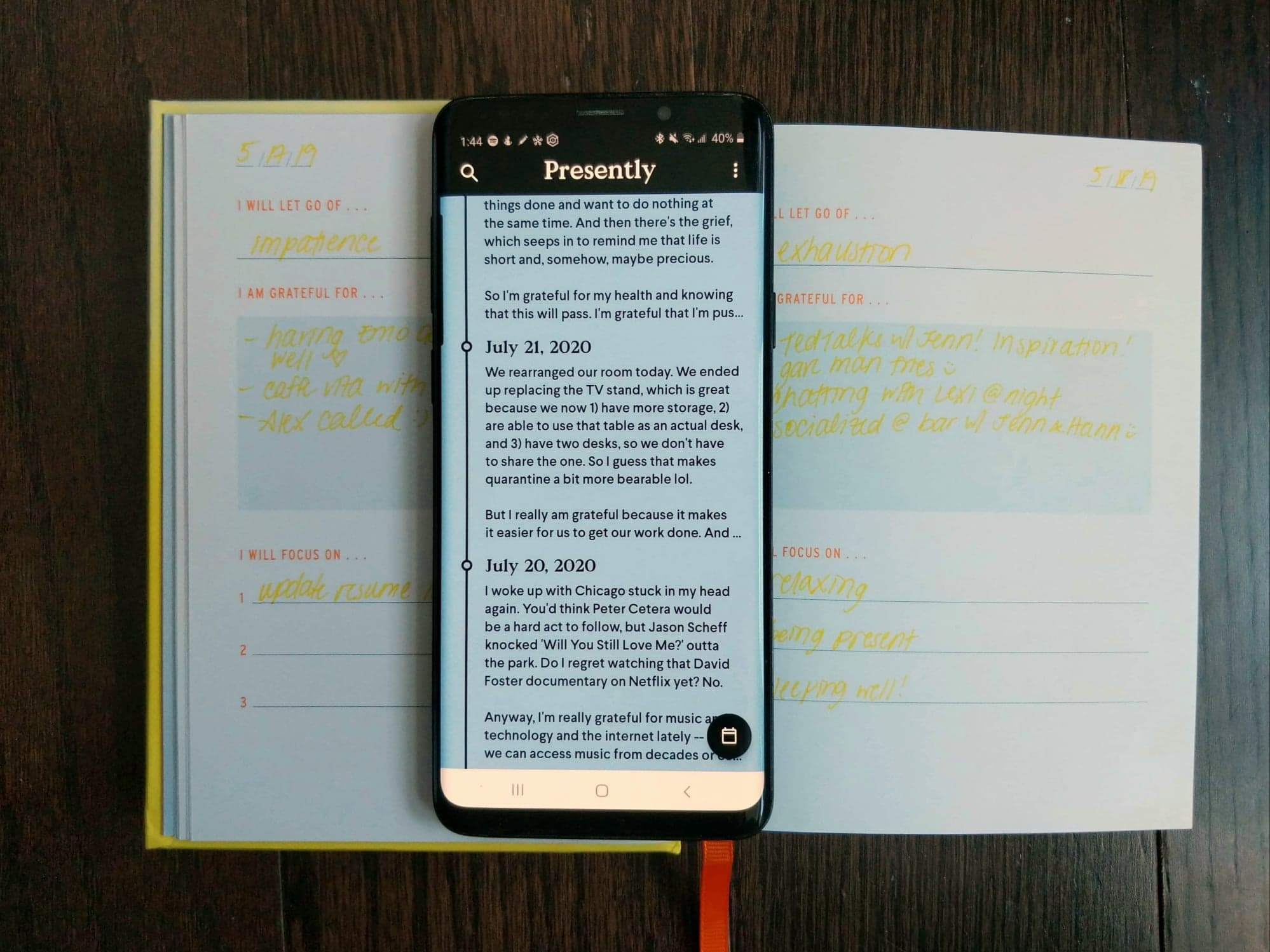 The writer's phone, showing recent entries in the Presently app, sitting on top of the open Two Minute Morning book that shows old entries from May 2019