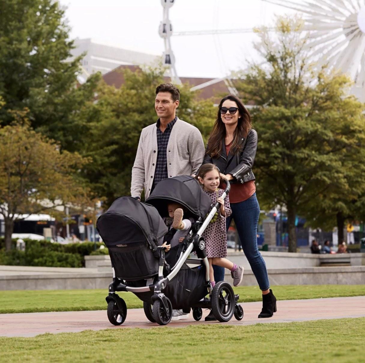family pushing black stroller