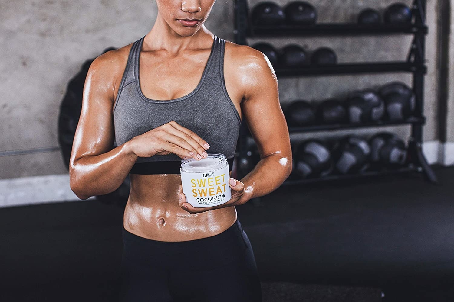 A glistening person applies the cream to their body before a workout