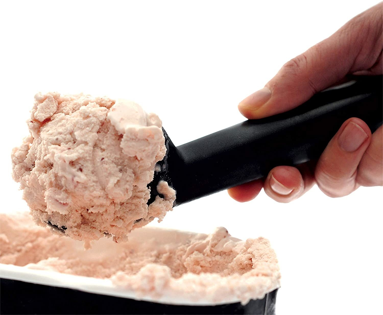 A person scoops ice cream out of a tub