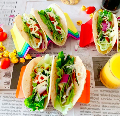 Pink, blue, green, yellow, and orange holders carrying tacos with all the fixings