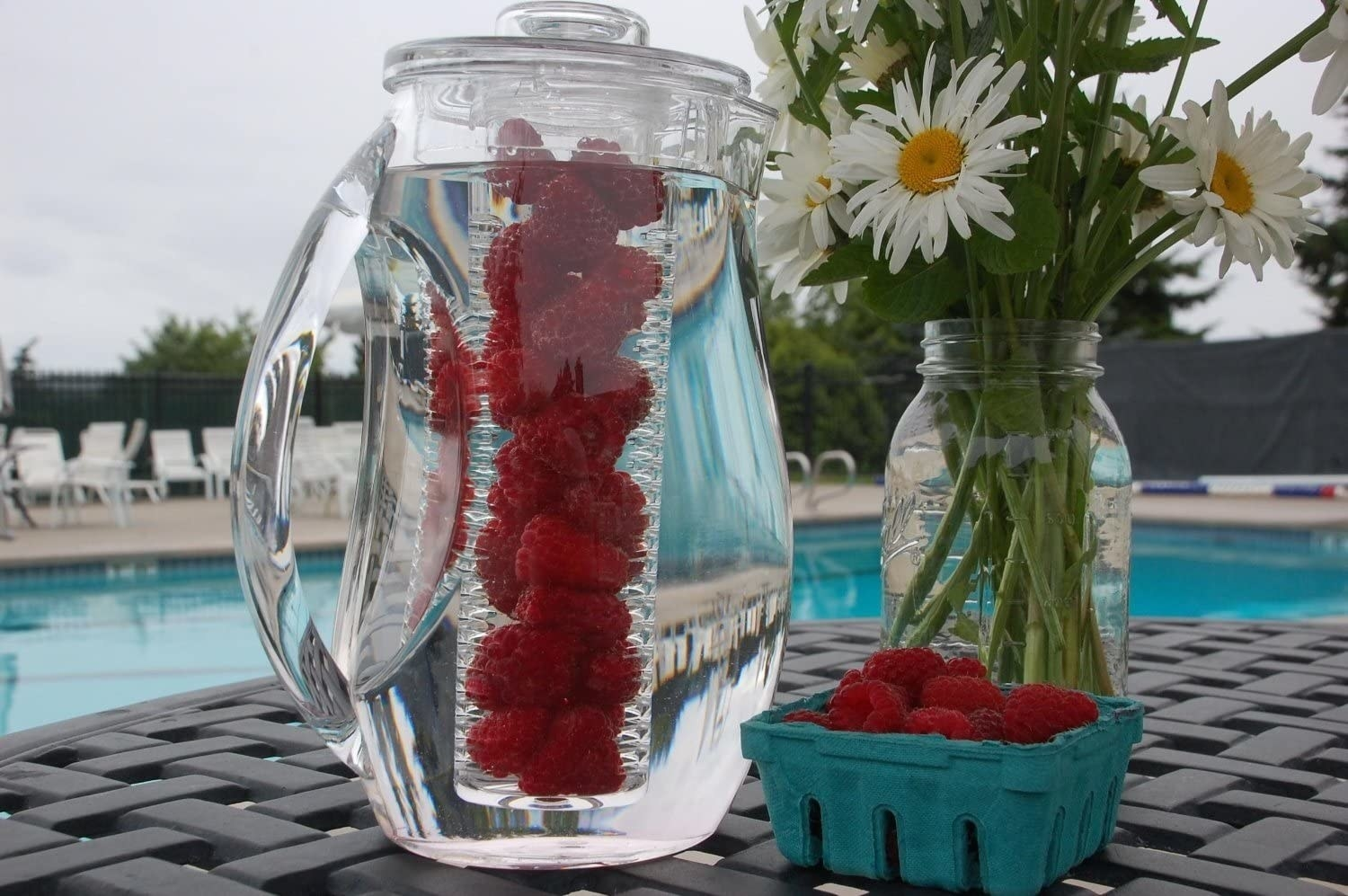 A clear fruit infuser pitcher with raspberries in the infuser