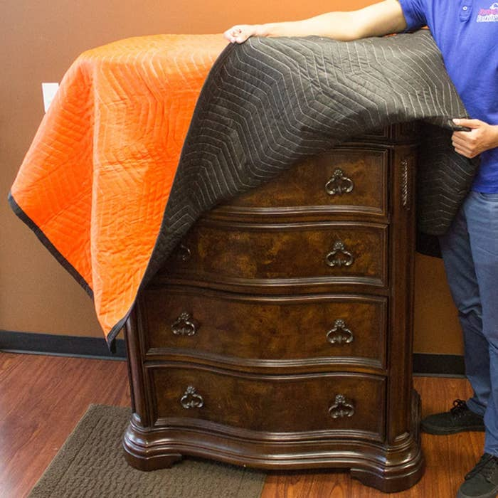 A model covering a wooden chest of drawers with and orange and black moving blanket