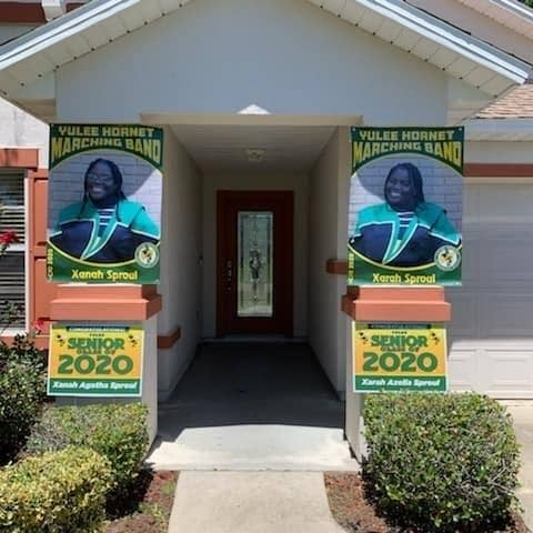 Photo of the front of Sproul home, which shows the two posters of Xanah and Xarah in their marching band uniforms.