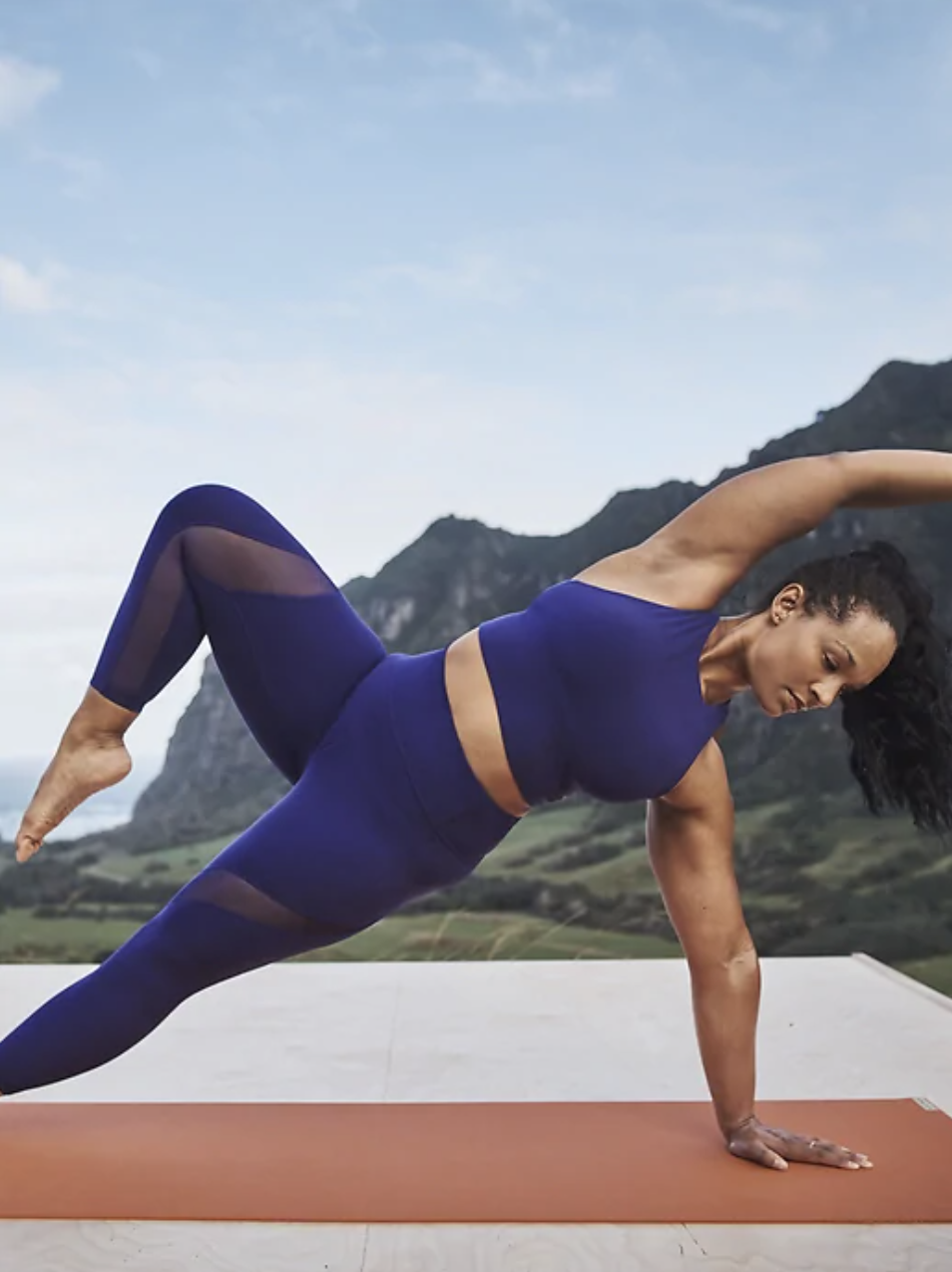 Model wearing the crop in bright blue while doing a side plank yoga pose