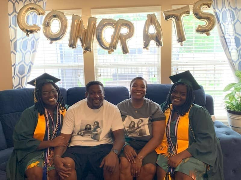 "Photo of the twins and their parents on a couch with a sign saying ""congrats"" behind them."