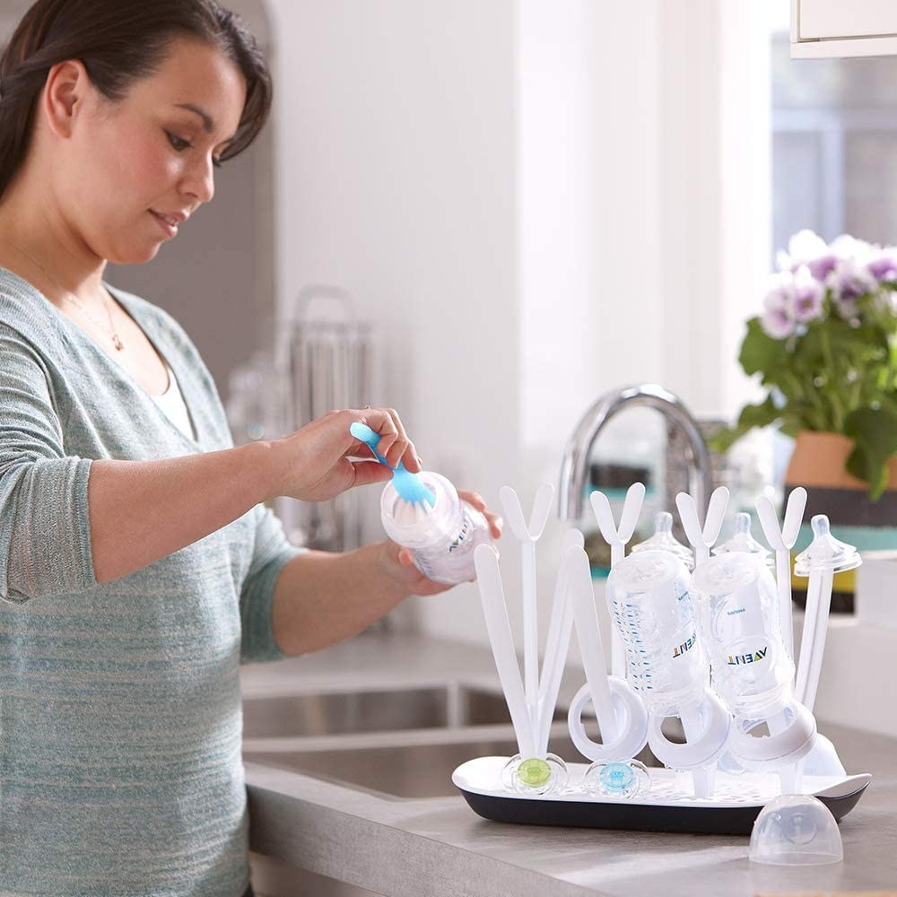 A person scrubs a baby bottle before putting it onto the drying rack