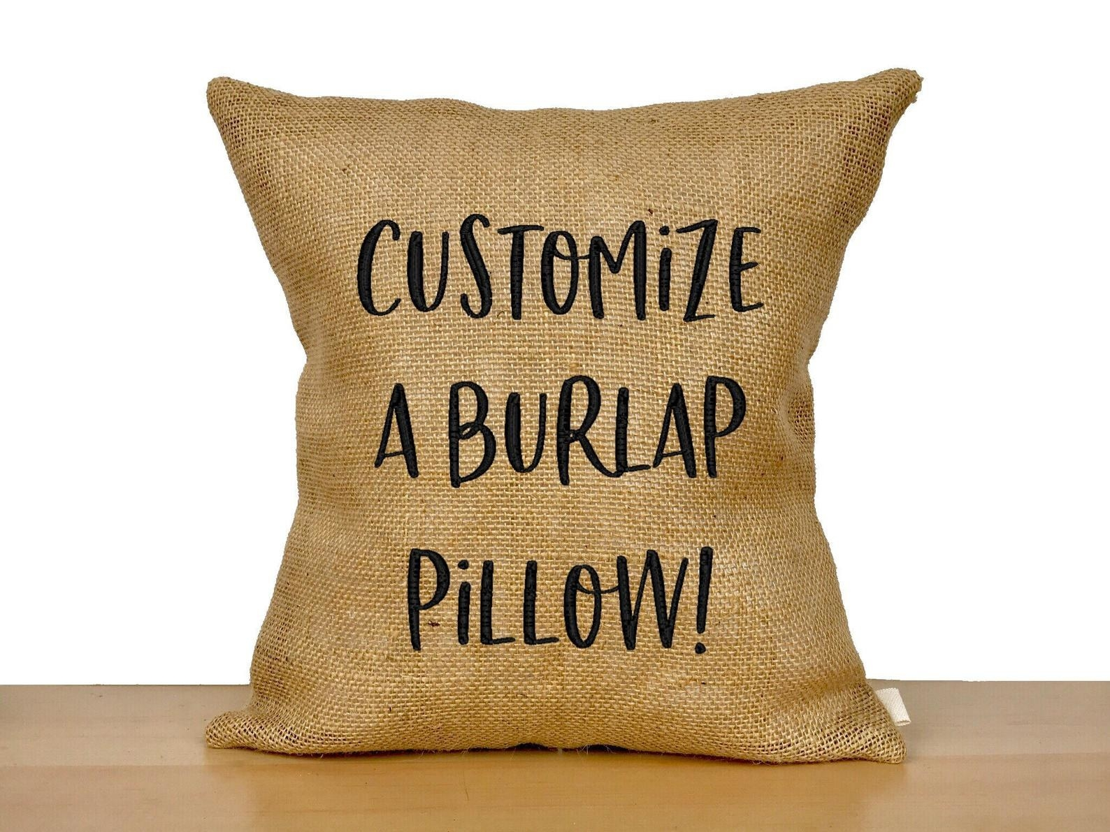 "A burlap pillow with the words ""Customize A Burlap Pillow!"" in black embroidery"