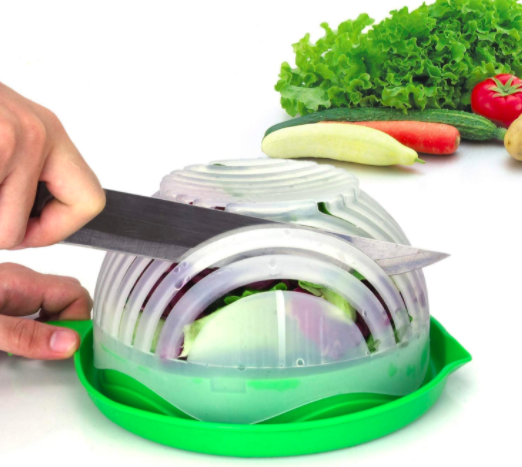 Hand dices lettuce while using a green and white salad chopper