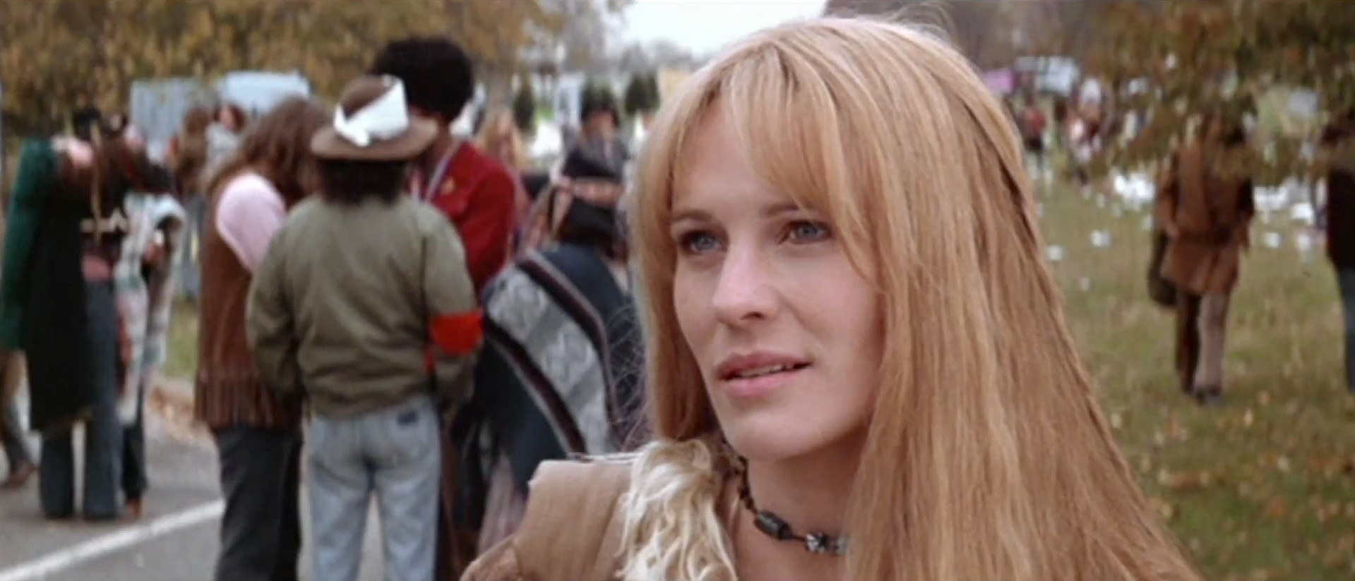 Jenny looking at Forrest, long hair wearing hippie clothes, happy to be reuniting with him at a protest in Washington, D.C