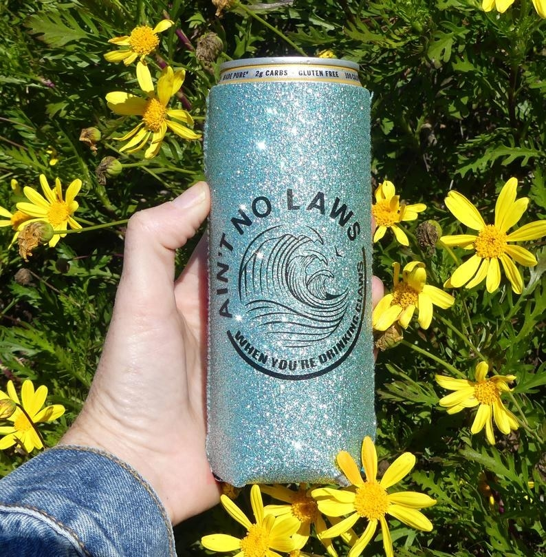 "A hand holding the blue glitter koozie that features the White Claw logo and the words ""Ain't no laws when you're drinking the Claws"" around it"