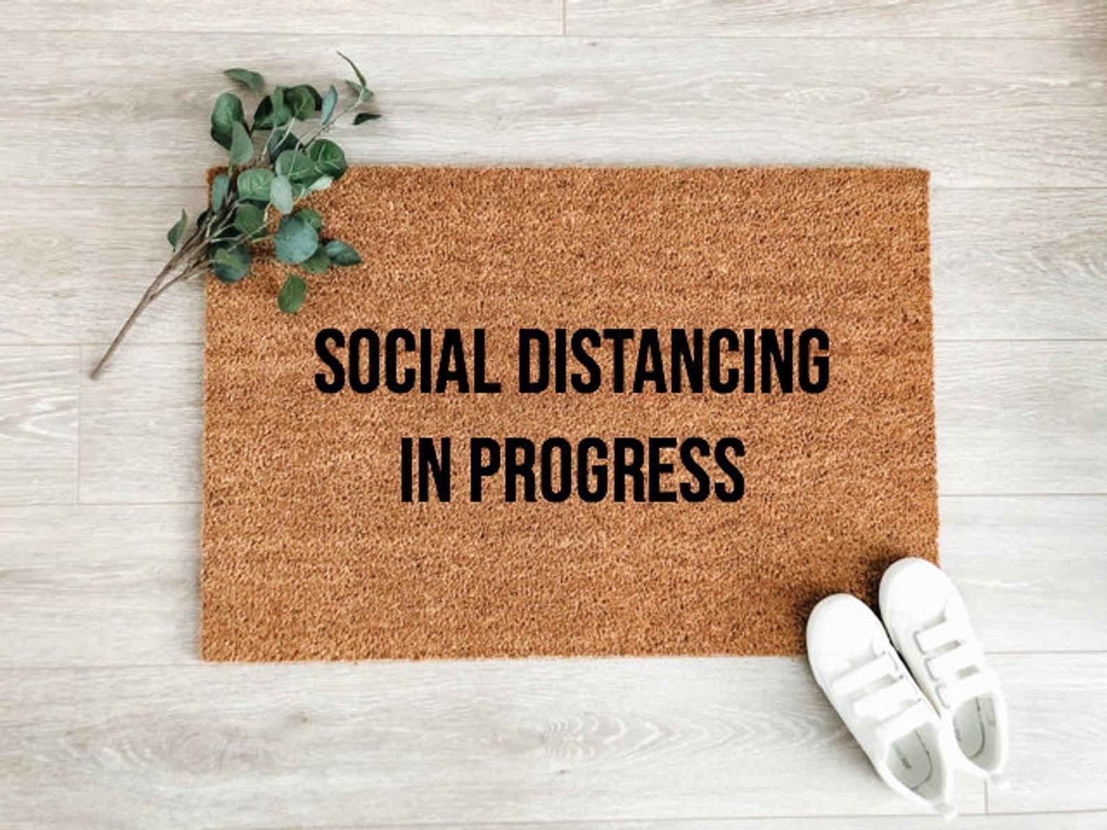 "A doormat that says ""social distancing in progress"""