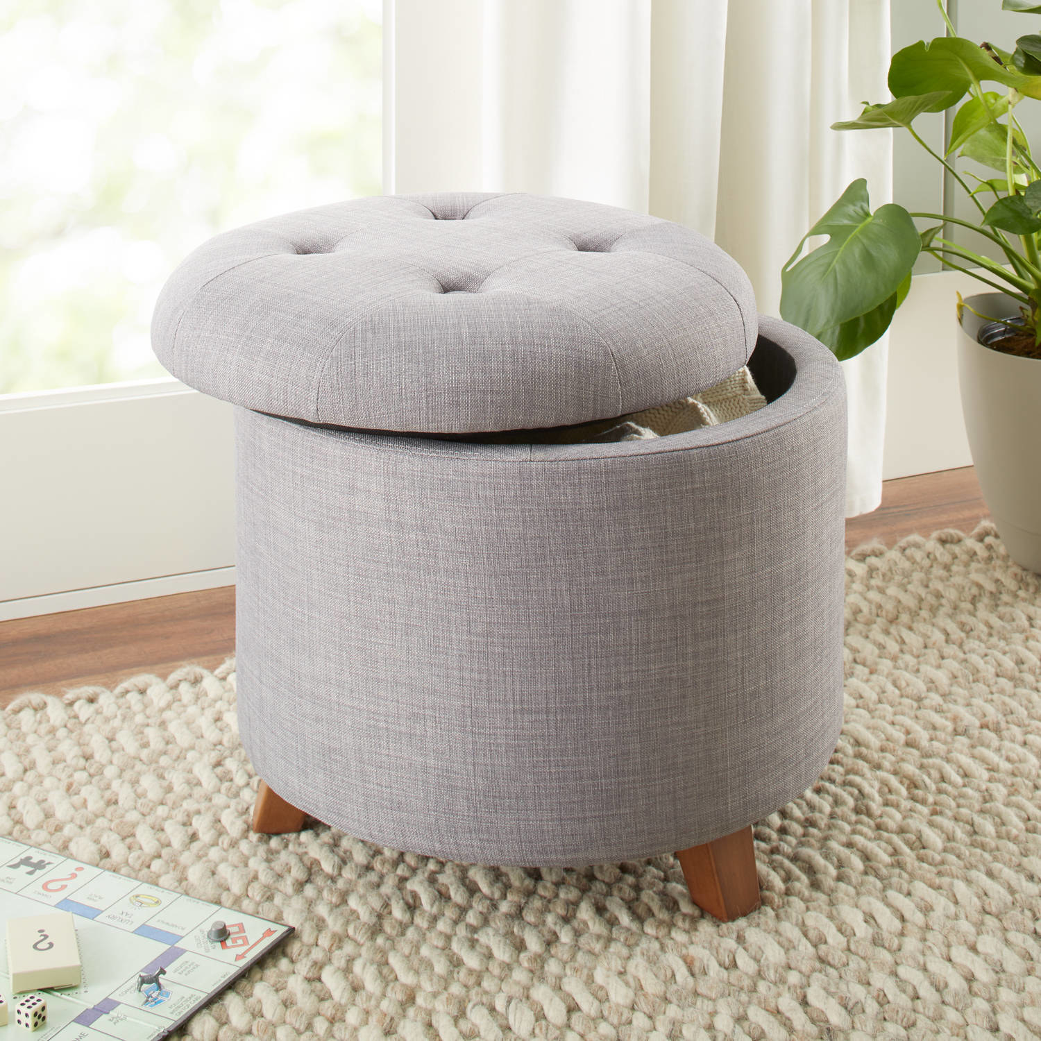 a grey circular tufted ottoman with brown legs