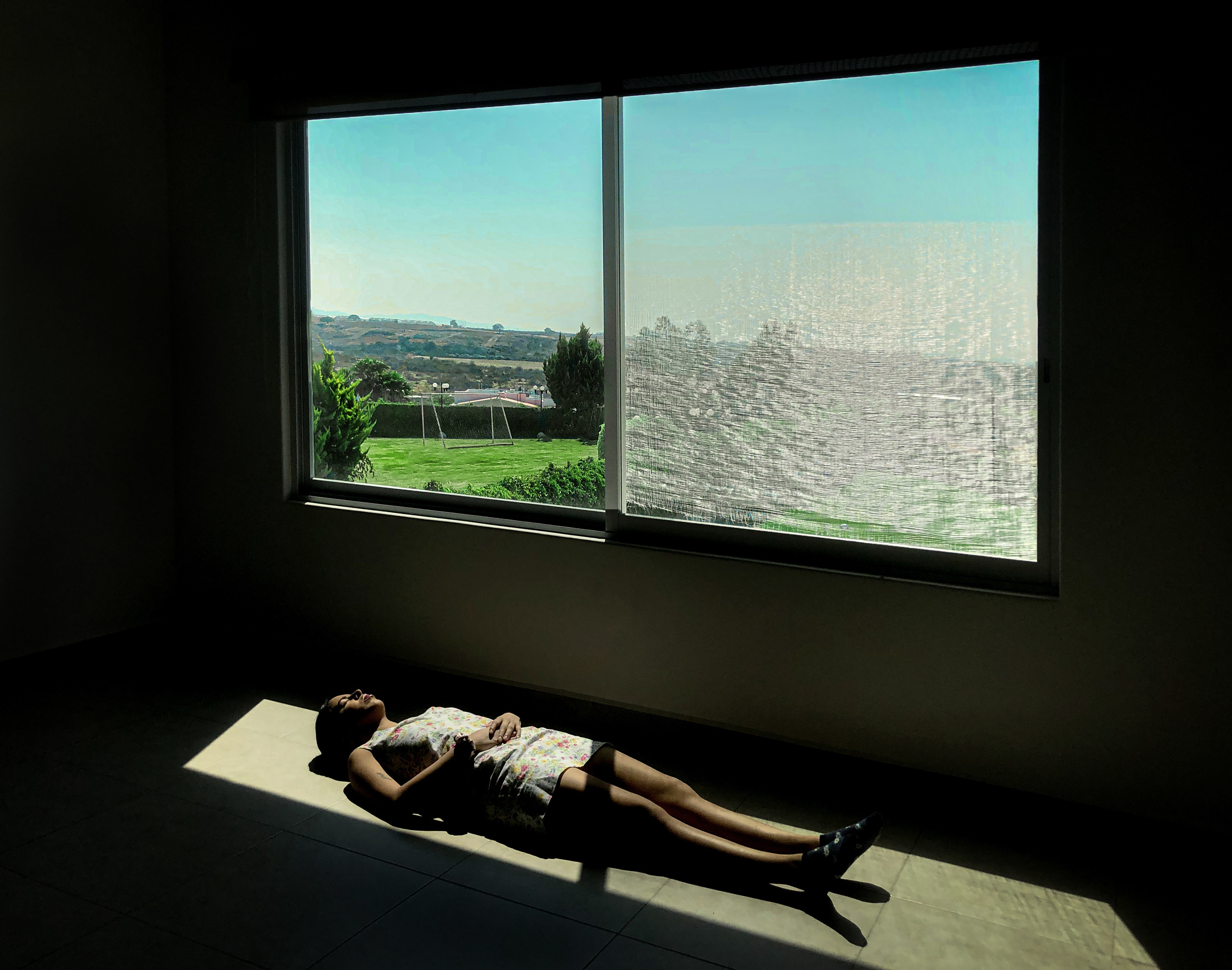A woman lies on the floor in a patch of light next to a window