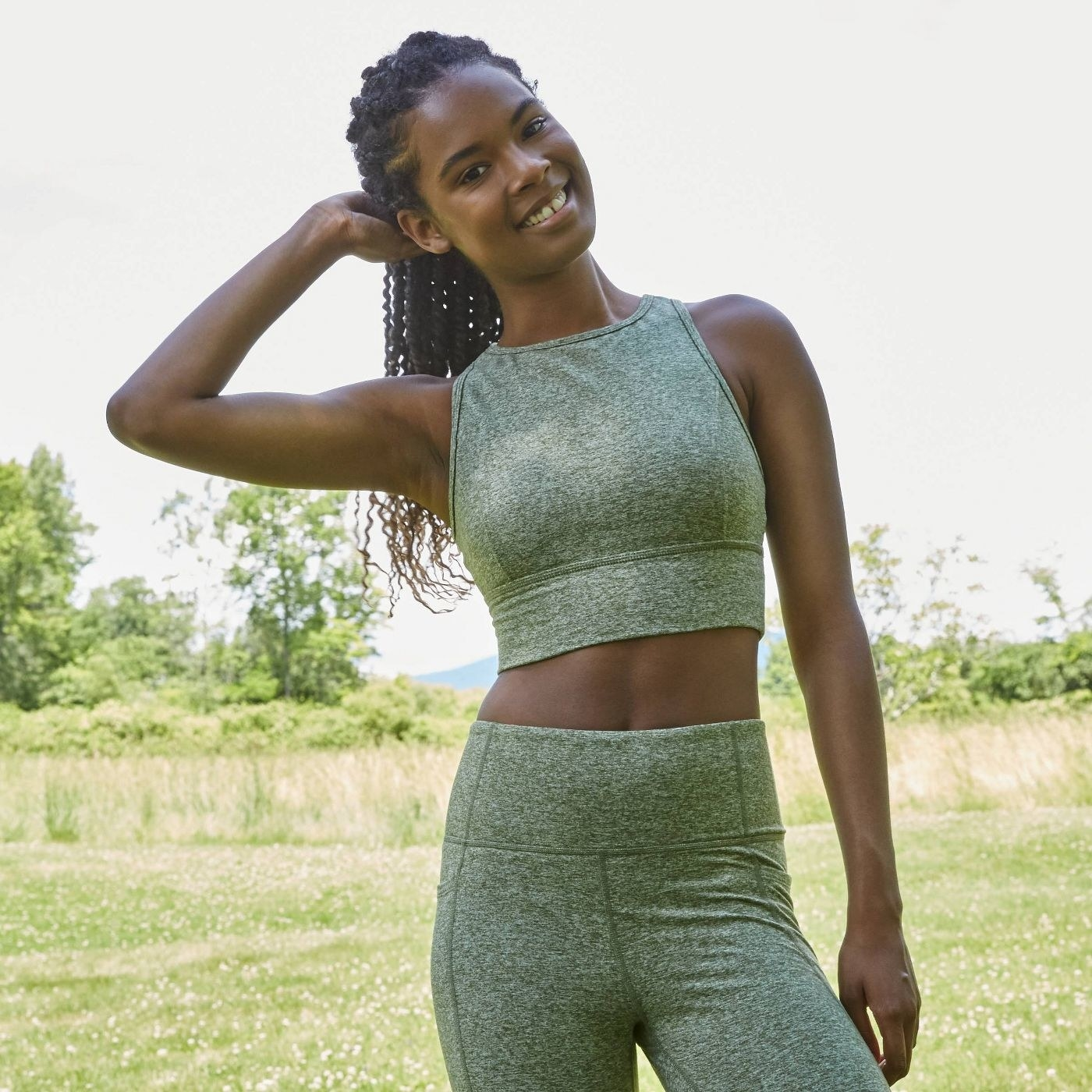 Model wearing the bra in heathered green with the matching leggings