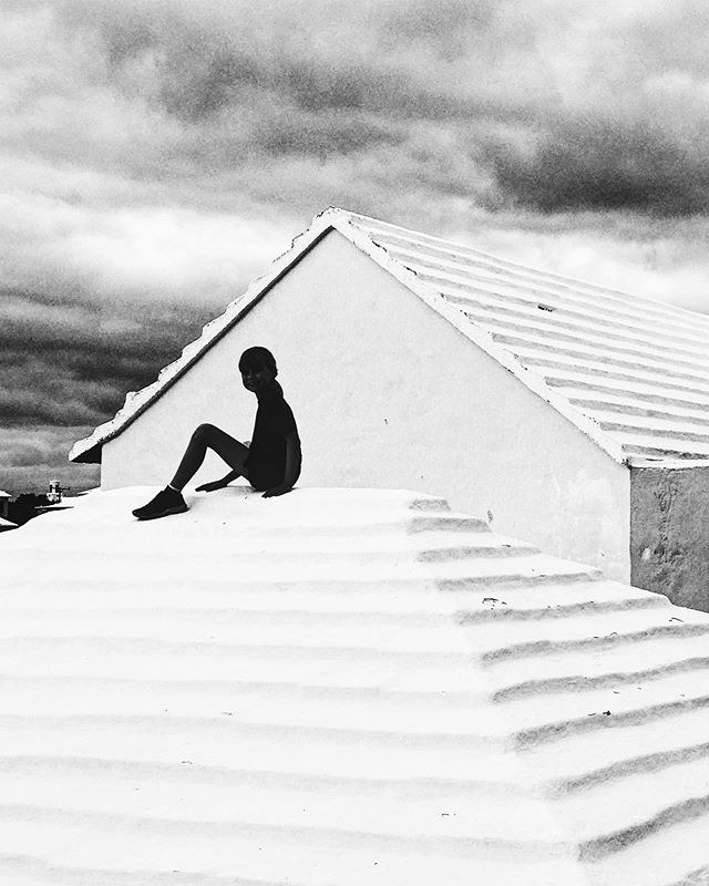 A child in silhouette sites on a roof