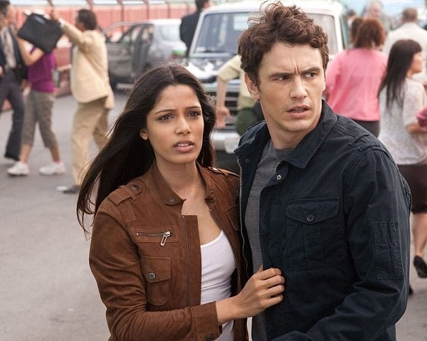 Freida Pinto as Caroline holds onto Will (James Franco) as to two look into the distance with worried expressions.
