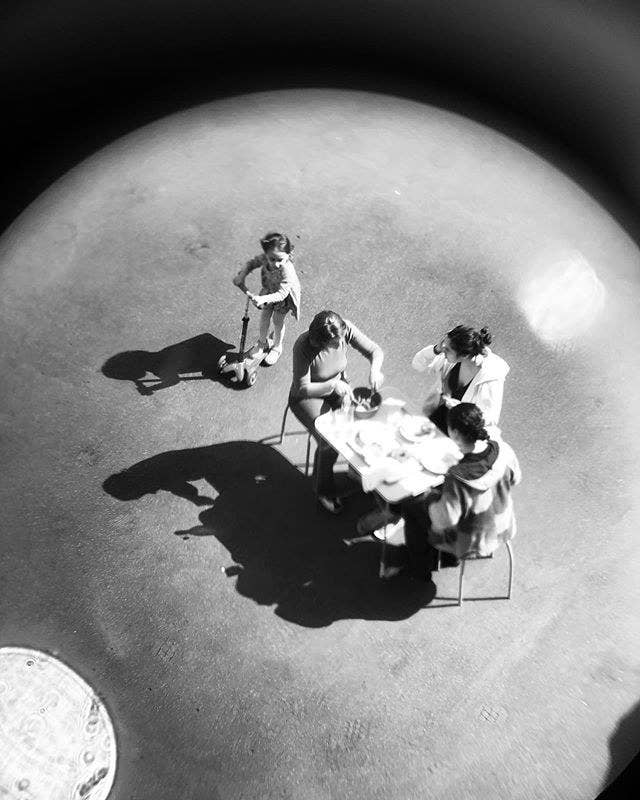 Family of four has dinner at a table through a long lens