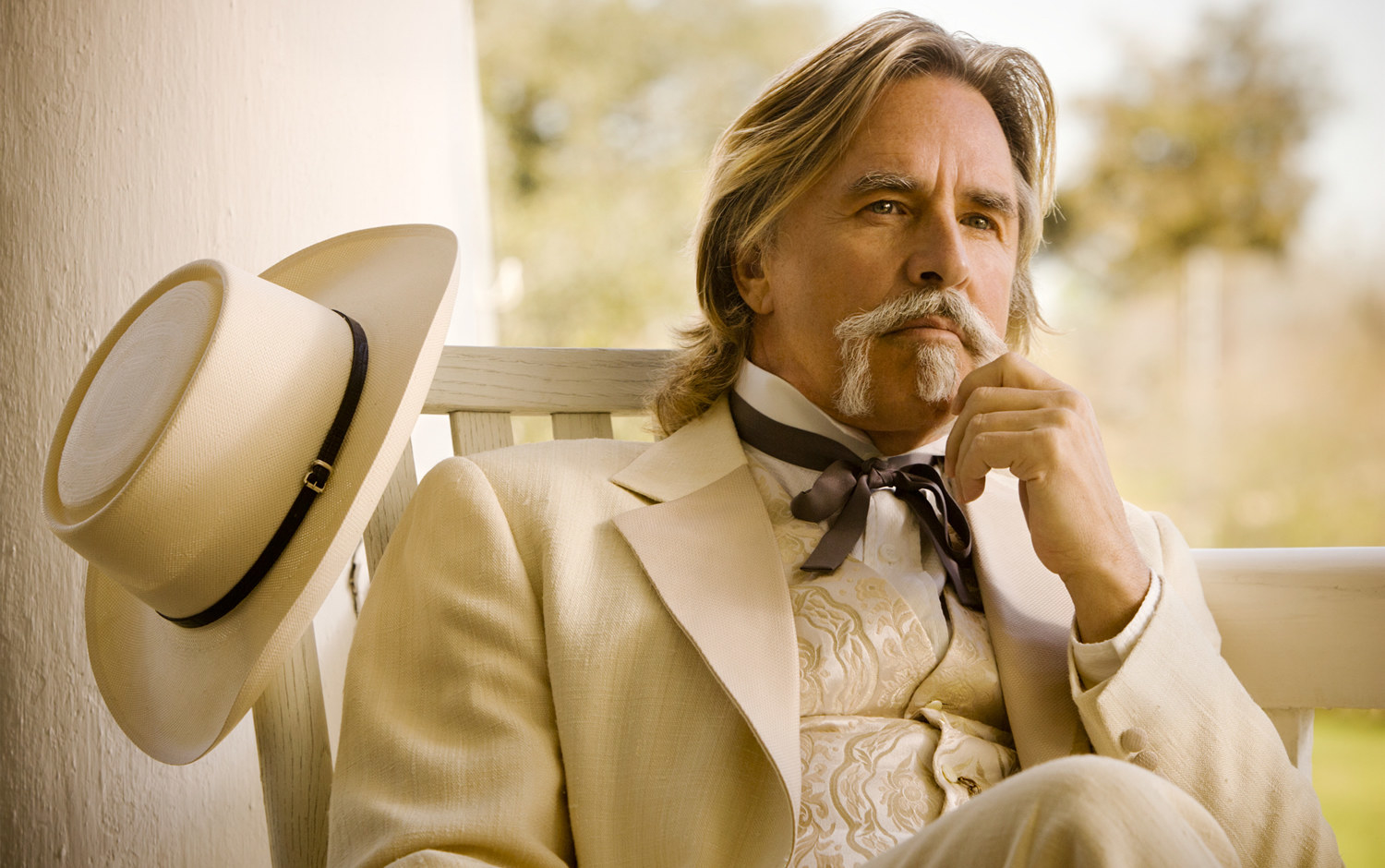 Don Johnson sits on an all white period suit on his porch on a sunny day. From the movie Django Unchained