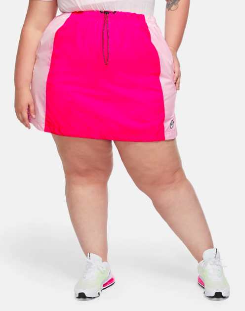 Model wears bright pink Nike bungee skirt with white and lime green sneakers