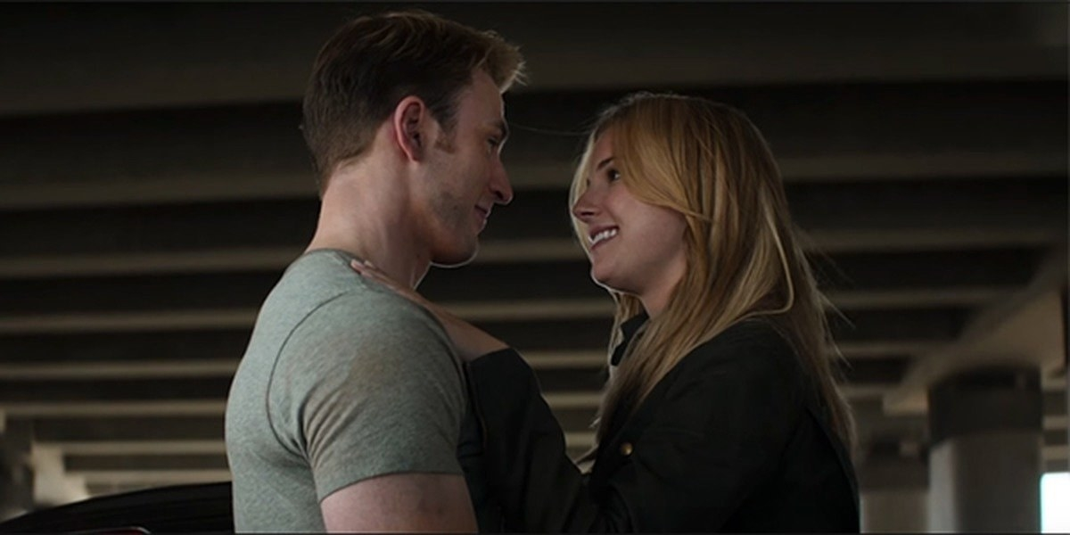 Chris Evans as Steve Rogers embraces and is about to kiss Sharon (Emily VanCamp).
