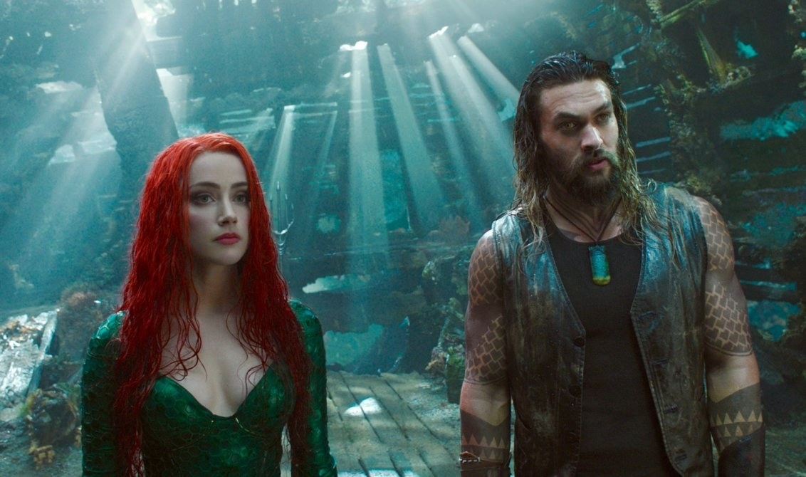 Jason Momoa as Aquaman stands side-by-side with Mera (Amber Heard) under water.