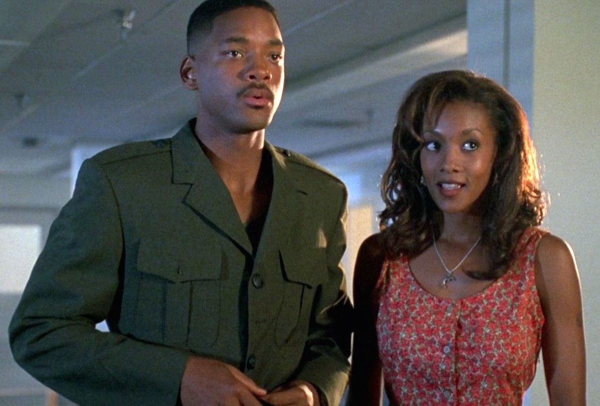 Will Smith as Steven and Vivica A. Fox as Jasmine stand next to each other looking confused.